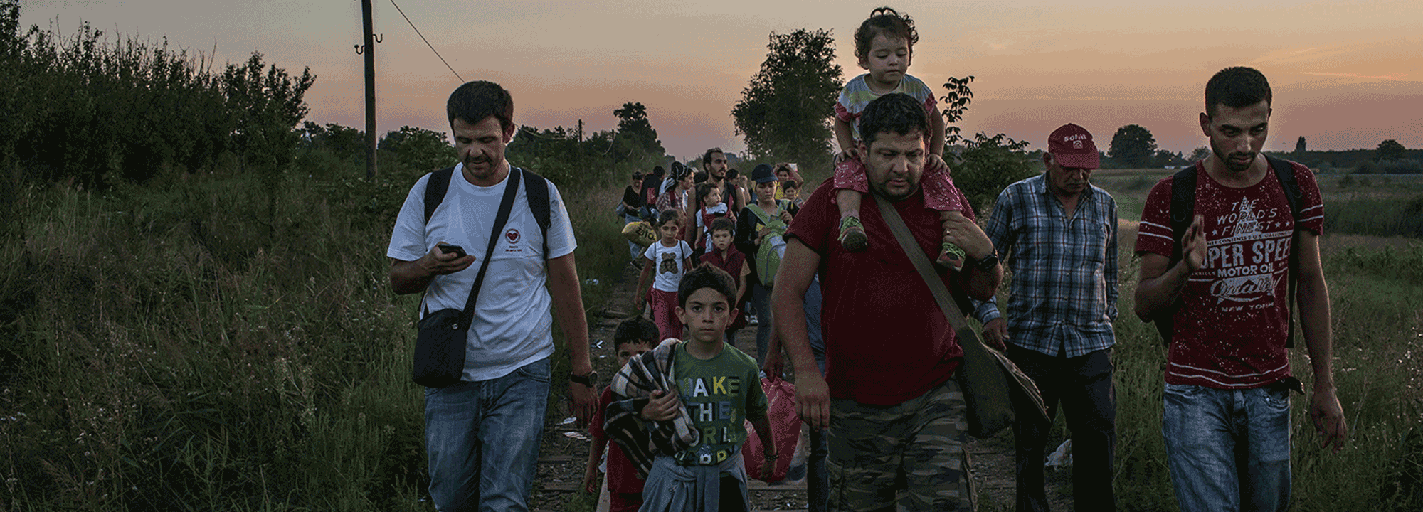 Horgos, Serbia - August 30, 2015: Farid Majid carries his daughter Silva on his shoulder next to his son Nabih, center, as Farid's brother Ahmad Majid, at left, checks his phone while walking down the railway with their relatives towards the Hungarian border, in Horgos. CREDIT: Photo by Mauricio Lima for The New York Times