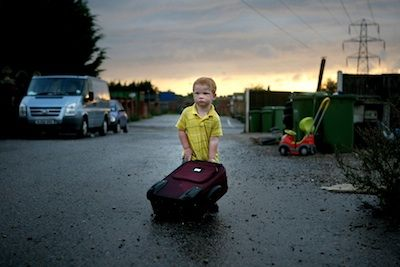 Dennis Sheridan, aged 3 years, plays with a suitcase that he found at Dale Farm, from which he and his family were evicted one month after this photograph was taken. Photographed by Mary Turner on September 11th 2011.