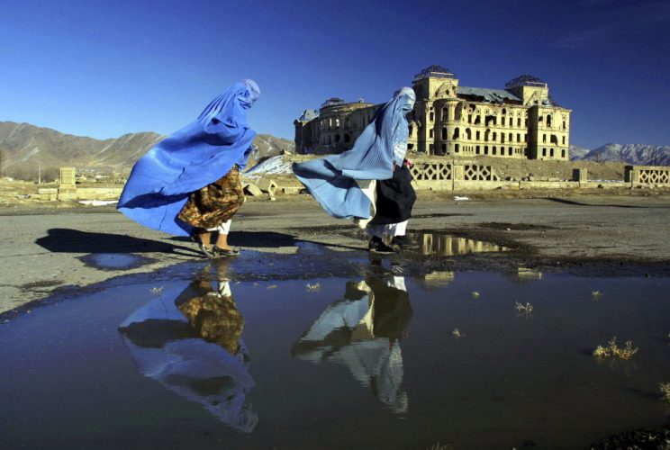 Afghan women in burqas walk in front of the Darulaman Palace in Kabul, Afghanistan on February 3, 2002 on a breezy winter day. The palace lies in ruins, it once was the materpiece of Kabul built by King Amanullah.