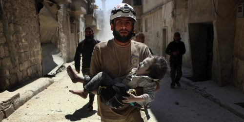 A White Helmets volunteer in Aleppo carries an injured child after an airstrike